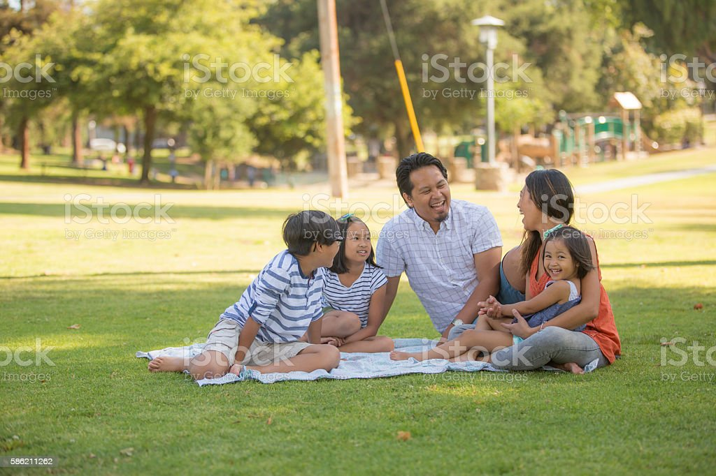 A happy Asian family spending time together in the park. stock photo
