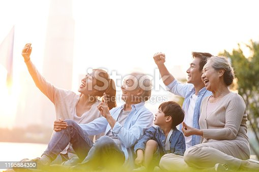 istock happy asian family taking a selfie outdoors 1195884350