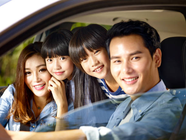 happy asian family traveling by car stock photo