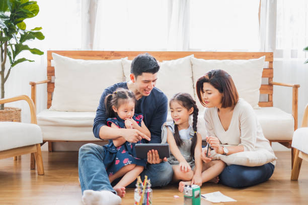 Happy Asian family using tablet, laptop for playing game watching movies, relaxing at home for lifestyle concept stock photo