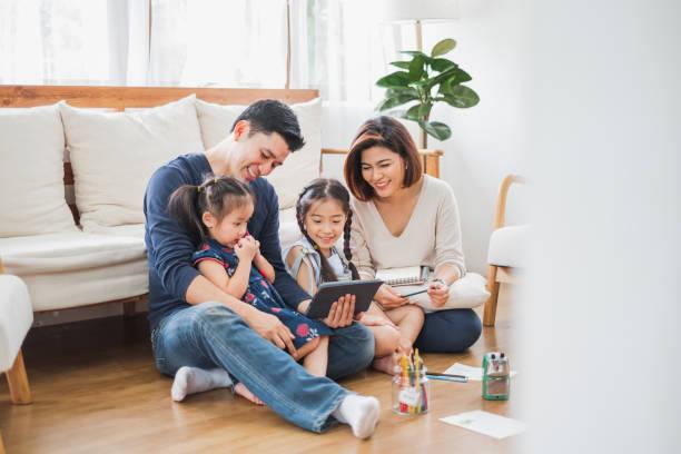 快樂的亞洲家庭使用平板電腦,筆記本電腦玩遊戲看電影,放鬆在家裡的生活方式概念 - 亞洲 個照片及圖片檔