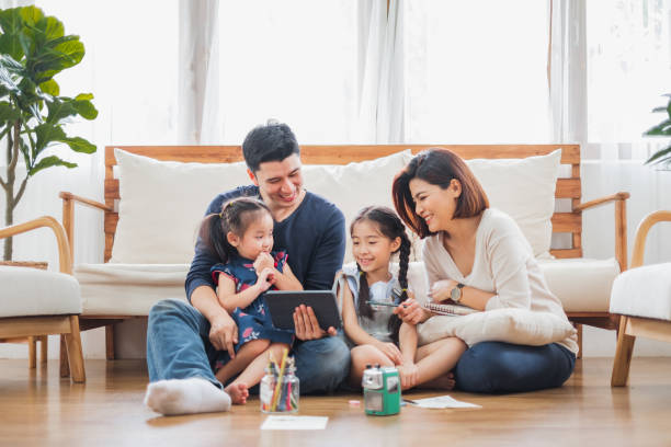 happy asian family using tablet, laptop for playing game watching movies, relaxing at home for lifestyle concept - ásia imagens e fotografias de stock