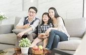リビングルームのソファーで一緒にテレビを見て幸せなアジアの家族。家族および家の概念。
