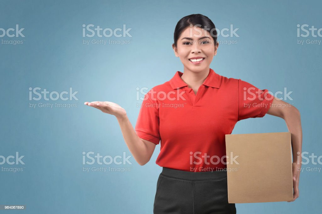 Happy asian female courier holding package - Royalty-free Adult Stock Photo