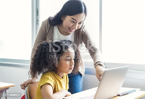 Happy Asian female teacher helping school kids using laptop computers in IT class. Education, elementary school, learning and technology concept.