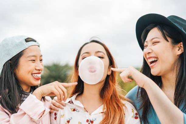 happy aziatische vrienden plezier kauwen kauwgom outdoor - jonge mensen spelen en lachen samen - vriendschap, duizendjarige generatie en levensstijl jeugdconcept - kauwgom stockfoto's en -beelden