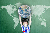 Happy Asian girl child student raising globe on school chalkboard for world literacy and gender equality concept. Elements of this image furnished by NASA