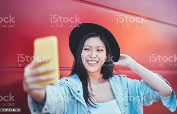 Happy asian girl doing a video story with mobile smart phone outdoor picture id1129960763?b=1&k=6&m=1129960763&s=612x612&h=uzyei2qyoved nyjvap75fn1zgyupre5otqexmkmrpi=