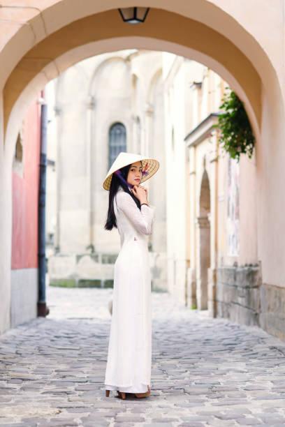 glückliches asianisches mädchen in traditionellen ao dai weißen kleid mit vietnamese konischen hut non la, leaf hut gekleidet. - hofkleider stock-fotos und bilder