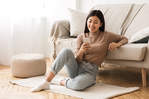 istock Happy Asian Girl Messaging on Phone at Home 1162300823