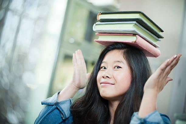 glücklich asiatische mädchen-student balancing stapel von büchern über kopf. - bücherbund stock-fotos und bilder