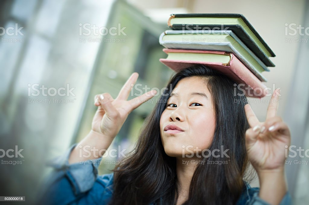 Happy Asian girl student balancing stack of books on head. stock photo
