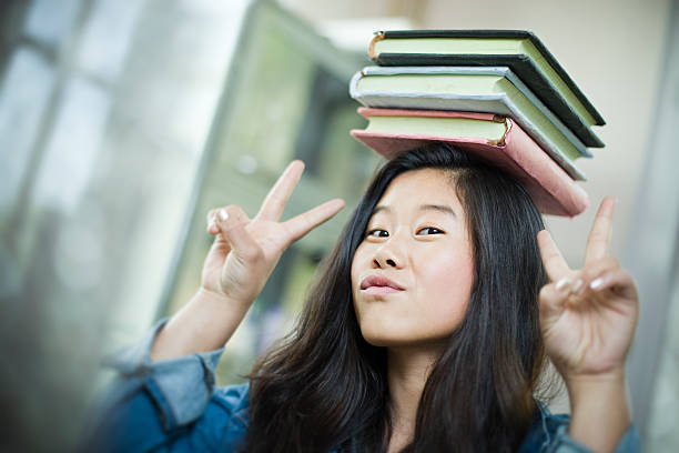 studente felice ragazza asiatica in equilibrio pila di libri sulla testa. - esame maturità foto e immagini stock