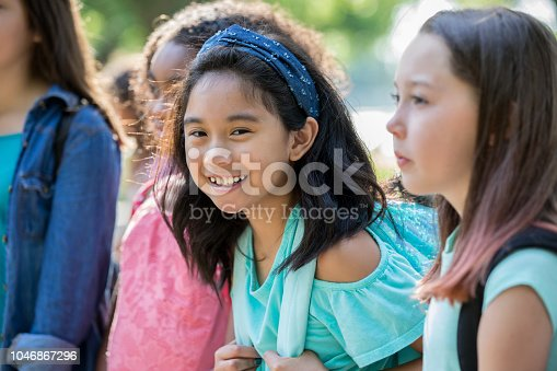 A happy middle school age little girl is smiling and looking at the camera. She is wearing a backpack, and waiting outside her school with a group of friends.