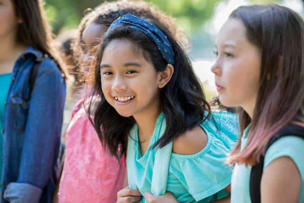Happy Asian girl wearing backpack outside school A happy middle school age little girl is smiling and looking at the camera. She is wearing a backpack, and waiting outside her school with a group of friends. cute middle school girls stock pictures, royalty-free photos & images