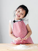 istock Happy Asian girl with pink apron preparing flour for cookie or pizza dough, lifestyle concept. 1126035307