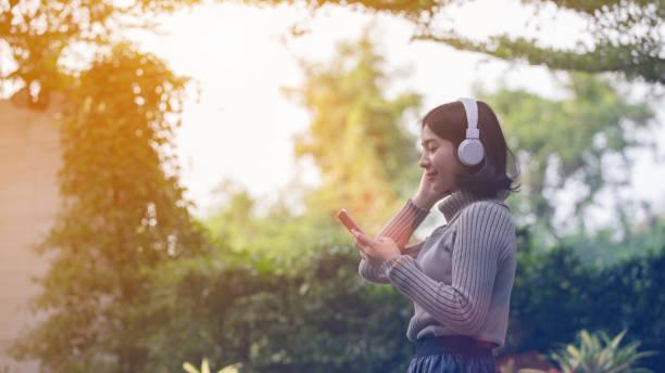 Im Park sind glückliche Asiatinnen Musikhören. – Foto