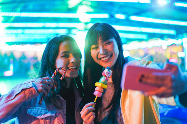 Happy asian girls eating candy sweets and taking selfie at amusement park - Young trendy friends having fun with technology trend - Tech, friendship and influencer concept - Focus on right female face stock photo