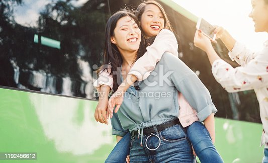 861023492 istock photo Happy Asian girls having fun outdoor - Millennial young people sharing time together and using mobile smartphone new trendy apps - Concept of friendship lifestyle with technology 1192456612