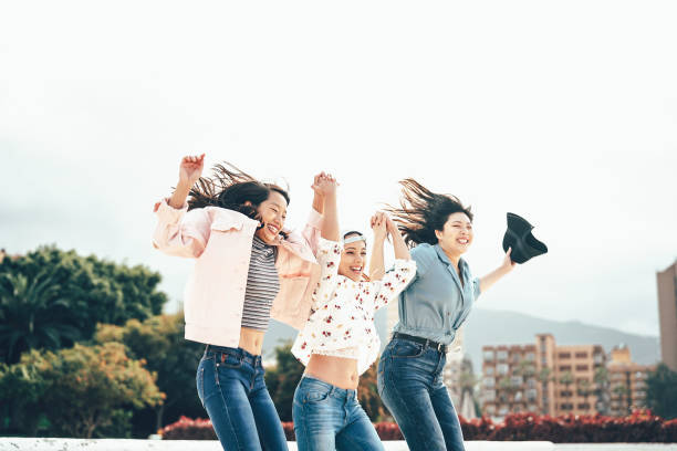 幸せなアジアの女の子が一緒に遊ぶ屋外-若い女性の友人は、大学の休憩ダンスを楽しんで、外千年世代、友情、若者のライフスタイルを祝う - 朝鮮半島 ストックフォトと画像