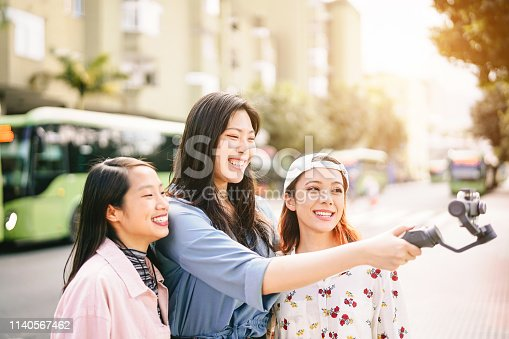 istock Happy Asian girls making video stories in the city center - Trendy young friends filming with gimbal smartphone  outdoor - Friendship, technology, youth people lifestyle and social media concept 1140567462