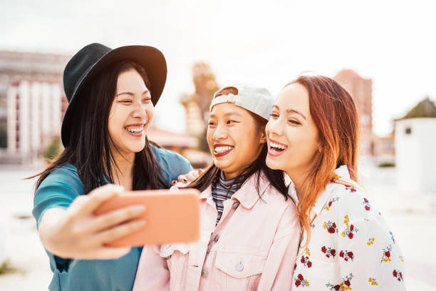 happy asian girls taking selfie with mobile smartphone outdoor - young trendy teenager having fun with new technology app - people, social, friendship, tech and youth lifestyle concept - philippines girl stock photos and pictures