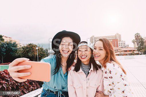 istock Happy Asian girls taking selfie with mobile smartphone outdoor - Young trendy teenager having fun with new technology app - People, social, media, friendship, tech and youth lifestyle people concept 1139074907