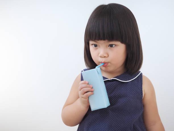 Jeune fille heureux enfant asiatique, boire du lait de boîte en carton avec paquet de jus de paille, blanc à la main des enfants en santé - Photo