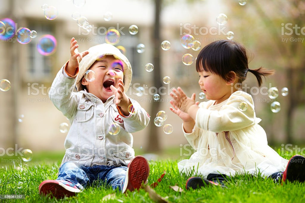 happy asian kids playing bubble together stock photo