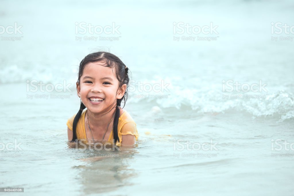 Happy asian little child girl having fun to play water in the sea in summer vacation stock photo