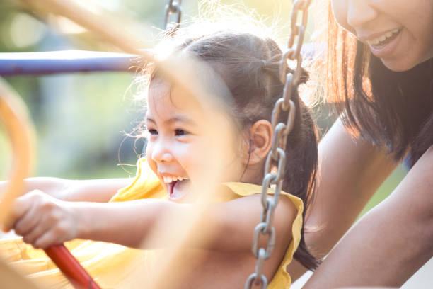 glückliche kleine kind asiatin spaß reitpony schaukeln wenn mutter schob ihr schaukeln - kinderspielplatz stock-fotos und bilder
