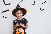 istock Happy asian little child girl in costumes and makeup having fun on Halloween celebration 1027435208