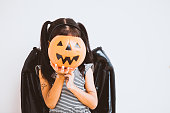 istock Happy asian little child girl in costumes and makeup having fun on Halloween celebration 1027435230