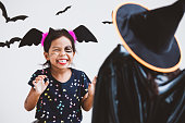 istock Happy asian little child girl in costumes and makeup having fun on Halloween celebration 1027435238