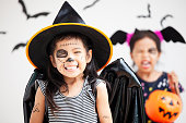 istock Happy asian little child girl in costumes and makeup having fun on Halloween celebration 1027435252