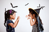 istock Happy asian little child girl in costumes and makeup having fun on Halloween celebration 1027435258
