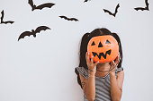 istock Happy asian little child girl in costumes and makeup having fun on Halloween celebration 1027435262