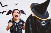 istock Happy asian little child girl in costumes and makeup having fun on Halloween celebration 1027435264