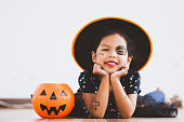 istock Happy asian little child girl in costumes and makeup having fun on Halloween celebration 1027435272