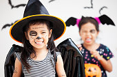 istock Happy asian little child girl in costumes and makeup having fun on Halloween celebration 1027435278