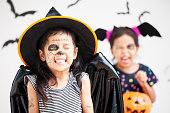 istock Happy asian little child girl in costumes and makeup having fun on Halloween celebration 1027435286