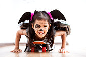 istock Happy asian little child girl in costumes and makeup having fun to play with roller board 1027435224