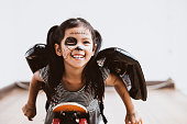 istock Happy asian little child girl in costumes and makeup having fun to play with roller board 1027435232