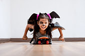 istock Happy asian little child girl in costumes and makeup having fun to play with roller board 1027435242