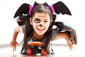 istock Happy asian little child girl in costumes and makeup having fun to play with roller board 1027435274