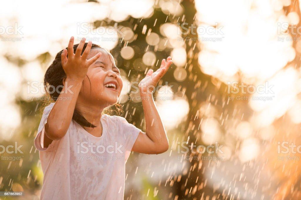 Menina asiática feliz se divertindo para jogar com a chuva foto de stock royalty-free