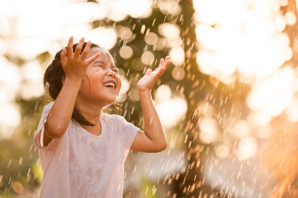 Happy asian little girl having fun to play with the rain stock photo