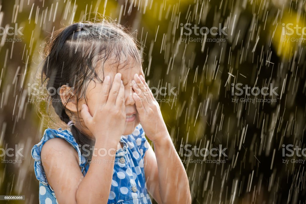 Happy asian little girl having fun to play with the rain in vintage...