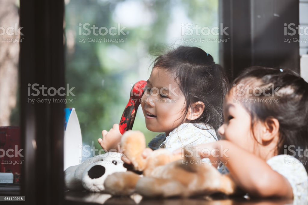 Happy asian little girl playing and talking phone in cafe royalty-free stock photo