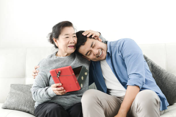 Happy Asian man giving gift box to his mother for Mother's Day celebration. Happy Asian man giving gift box to his mother for Mother's Day celebration. old mother son asian stock pictures, royalty-free photos & images